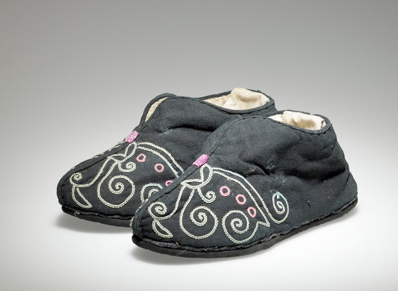 slipper-like shoes; back flap at heel-white on one side, blue gingham on opposite side; black with embroidered toes with green vine and leaf -like designs and pink circles; lined with white flannel
