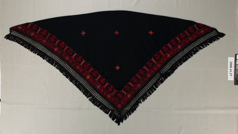 black fringed shawl; triangular shape; black fringe on two edges; wide band of cross stitch embroidery in reds with blue and yellow accents along fringed edges; four cross-shaped motifs in center area of shawl