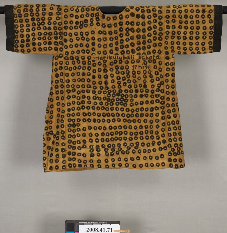 "khaki colored shirt with black hand painted circles simulating leopard spots; large bag-shaped pouch on front of shirt; chest high band across front with signature (by owner): ""Kelarikulubali Kabara""; ""yeniye"" written under last part of signature; medium length sleeves with painted black bands at bottom; open fabric band on PL shoulder on back"