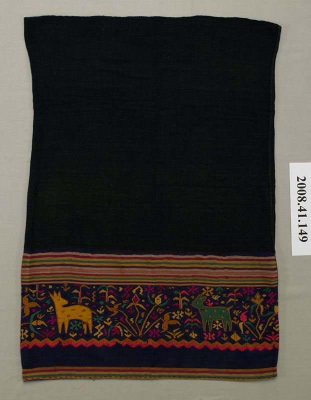 """black tube skirt in two sections; top section has plain black fabric; bottom section is dark purple with multicolored woven horizontal stripes; multicolored embroidery of deer-like animals, floral and foliate designs and insect-like motifs between two bands of stripes; two rows of zigzag embroidery below; 1"""" wide strip of tan fabric added at center back bottom section"""