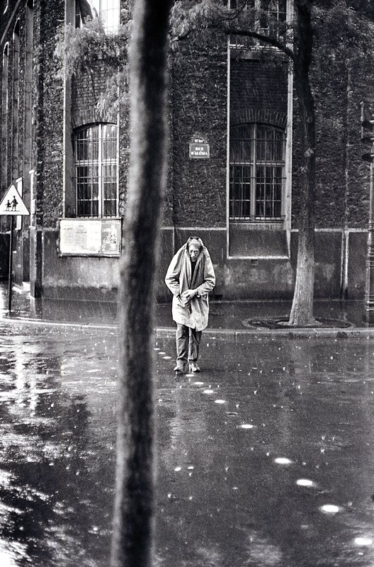 man crossing a street in the rain with coat pulled up over his head