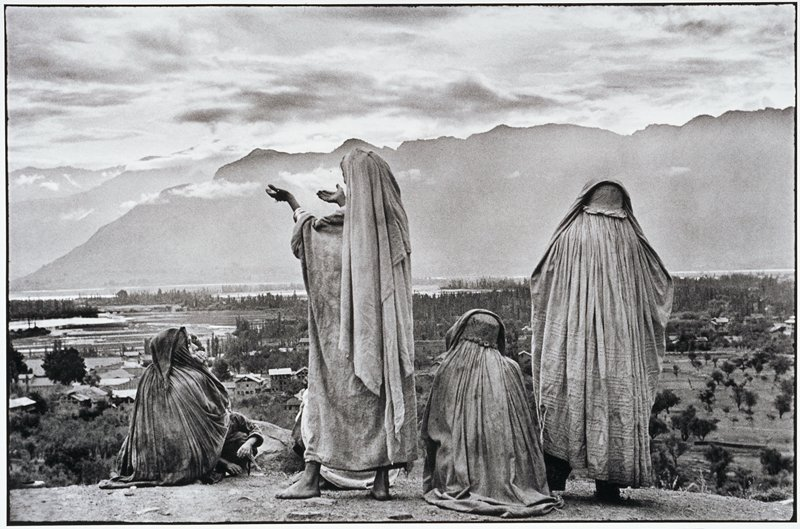 backs of four robed people standing on a hill over looking a valley, mountains in the background