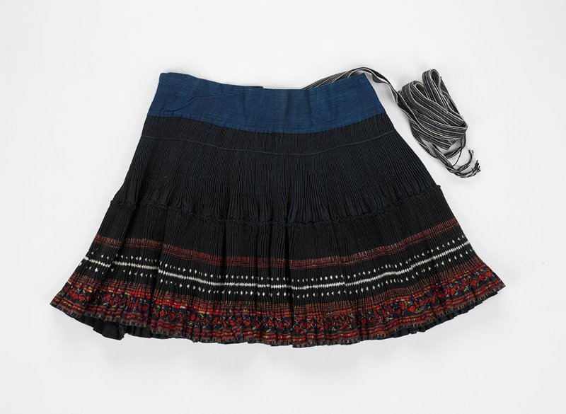 """pleated skirt; blue waistband with added ties of black and white ribbon-like fabric; skirt in two sections--top 6"""" (approx.) of dark blue; lower section of black with geometric embroidery in red, green, white and some gold; side panels of bottom section are plain blue without embroidery"""