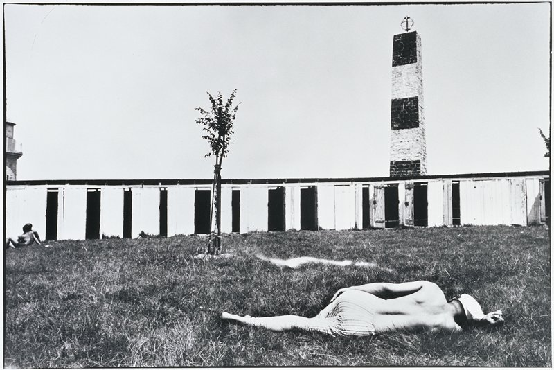 shirtless man lying in grass in front of a sapling; long horizontal building with doors and a striped brick tower