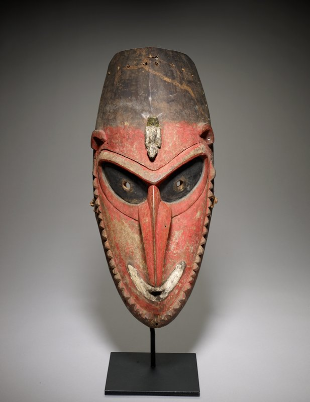 "very long, curved-under nose; large upward-slanting black eyes with perforated holes; smiling white mouth with small opening; small ""knobs"" represent beard; white bird on forehead; high-set ears with two piercings each; red patina on face; brown at top of head; ovoid shape overall"