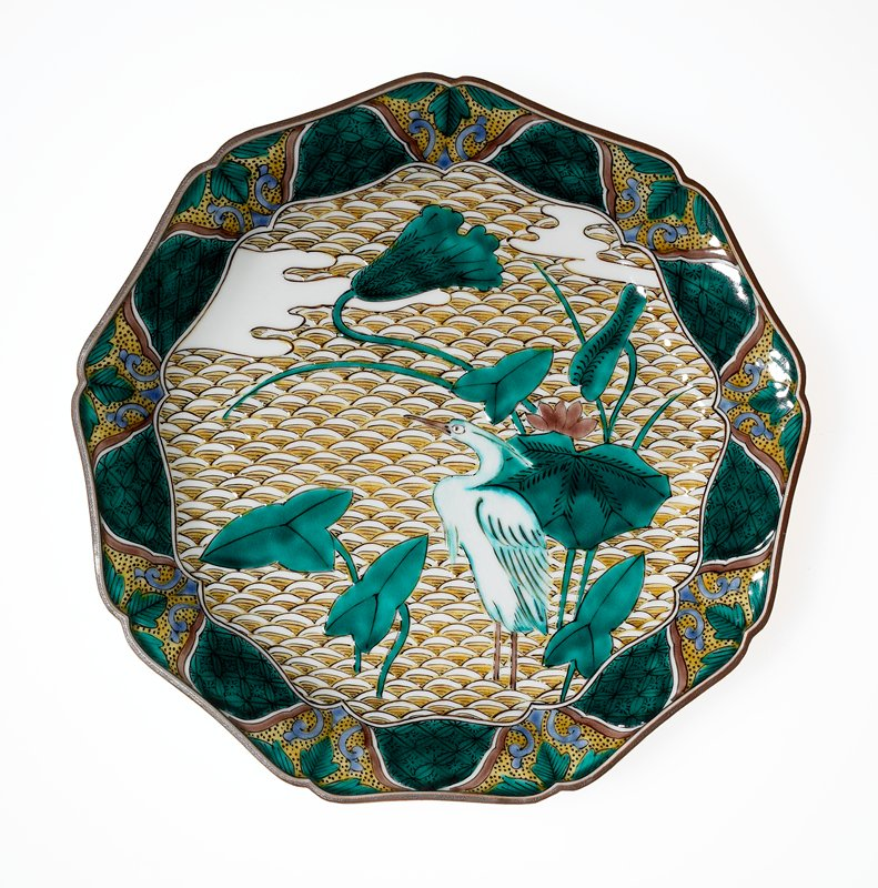 nine-sided plate on ring foot; articulated rim with indentations at corners; central design of crane and plants with very large green leaves; organic and geometric motifs on border; green, yellow, brown and purple glazes; three sprays with brown flowers and green leaves separated by small geometric cartouches on underside at rim; white ground
