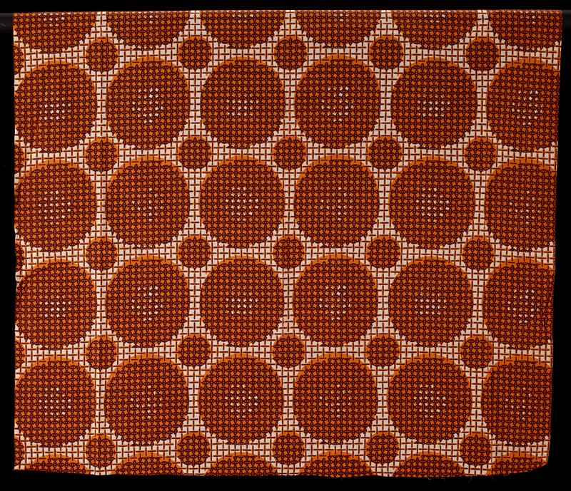 large and small orange circles covered with small brown oval print against basket weave pattern