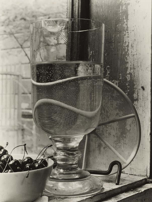 stemmed glass with clear liquid; bowl of cherries in lower left corner