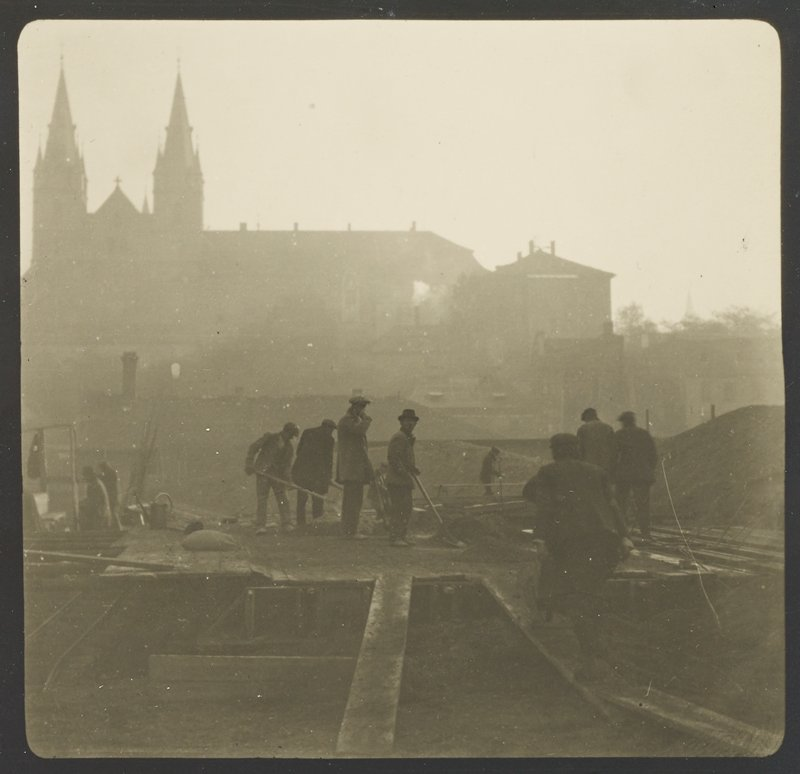 construction workers in middle ground; building with spires in background