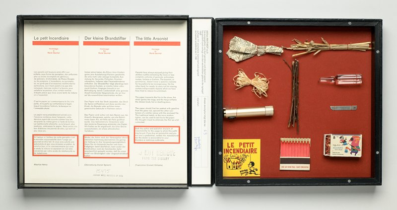 black clamshell box containing objects attached to red backing board with red thread, under a Plexi cover; objects are: small crumpled pieces of newspaper (with Greek text), bundle of straw, loops of raffia or other plant fibers, bundle of small sticks, bottle-shaped vial of clear liquid (gasoline?), cylindrical gold lighter, silver metal file, book of pink matches and box of wooden matches with cartoon image of a purse snatching; yellow card printed with cartoon drawing in red and black of a smiling boy watching a burning house