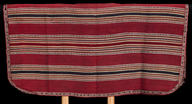 predominantly red with multicolored horizontal stripes; rounded corners; red, white and purple edging; six patterned stripes on each side; warp faced plain weave with complimentary warp weave decorative bands; added complimentary warp woven edge band