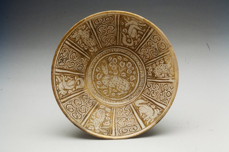 Bowl, white earthenware, enamelled in white. Decoration painted in gold luster consists of a hare amid scrolls surrounded by compartments with animals and arabesques.