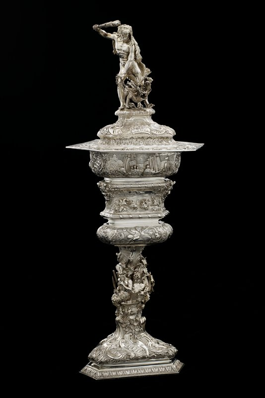 triangular with clipped corners; stemmed cup with footed base; removable liner; slightly domed cover with three-dimensional finial of male figure wearing lion skin, holding a club aloft, with a three-headed dog held by chains; stem has a satyr in three dimensions seated next to cattails; grape vines twisting behind satyr; Classical themes, hunting and battle scenes and various scrollwork overall in high and low relief