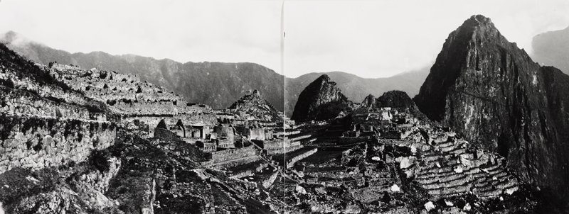 two photos attached together on back with Scotch tape; view of rugged mountains in background and ruins of Macchu Picchu