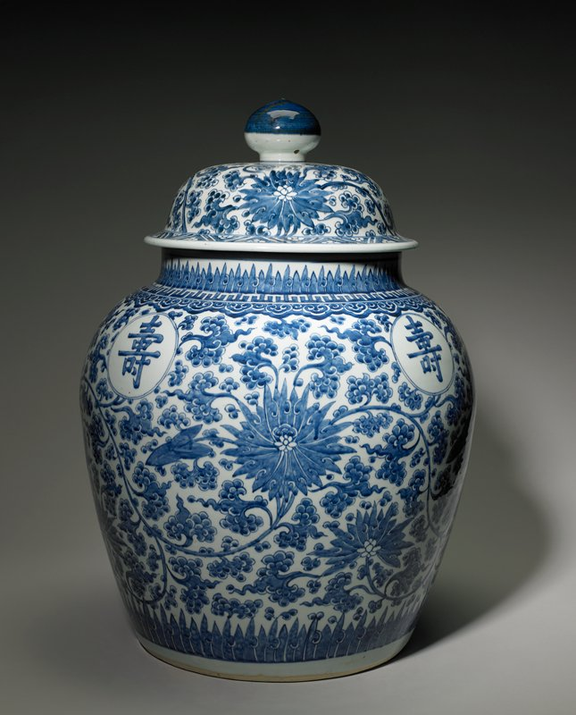 large blue and white jar with overall scrolling vine and flower motif; flame-like elements at top and bottom of jar; floral and zigzag band at bottom of cover; four round medallions on shoulder with Chinese characters; cartouche at rim with four Chinese characters