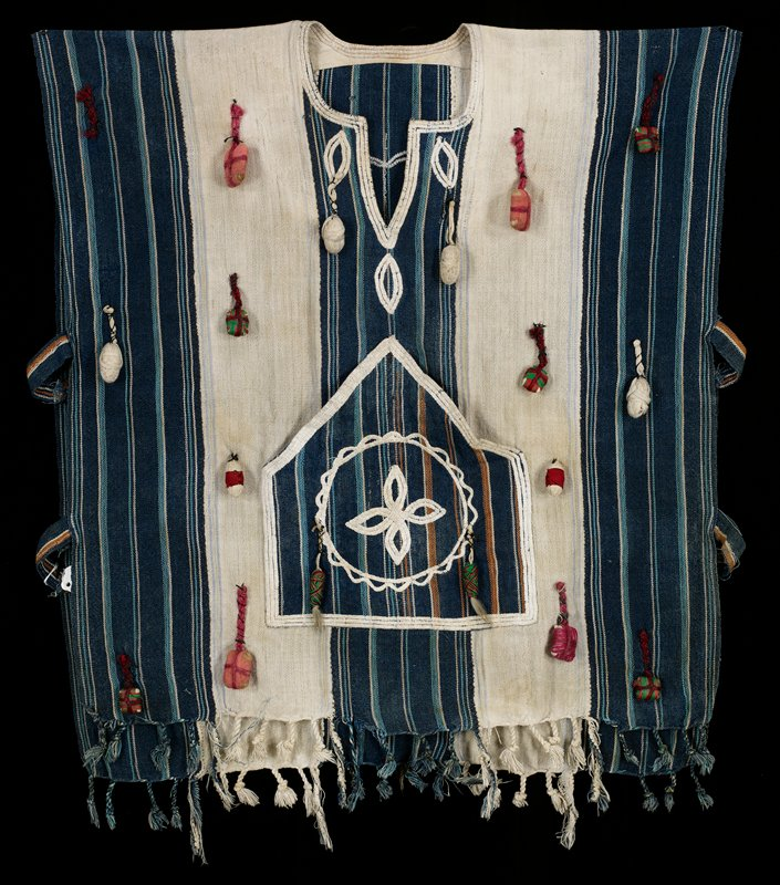 pull-over garment with open sides, with two horizontal fabric tabs on each side; blue, white and orange striped fabric; twisted and knotted fringe; pouch pocket decorated with round medallion stitched in white; white stitching around neckline; embellished overall with square and ovoid 3-D elements wrapped in thread or yarn of various colors; white heart stitched on back