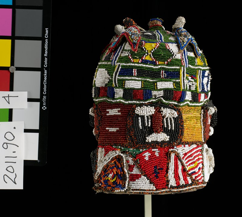 tall dome-shaped beaded hat; five bird-like shapes at top applied to surface; several areas of raised beaded designs on bottom two sections of beading (two on bottom row, four and second row); motifs overall are mostly geometric