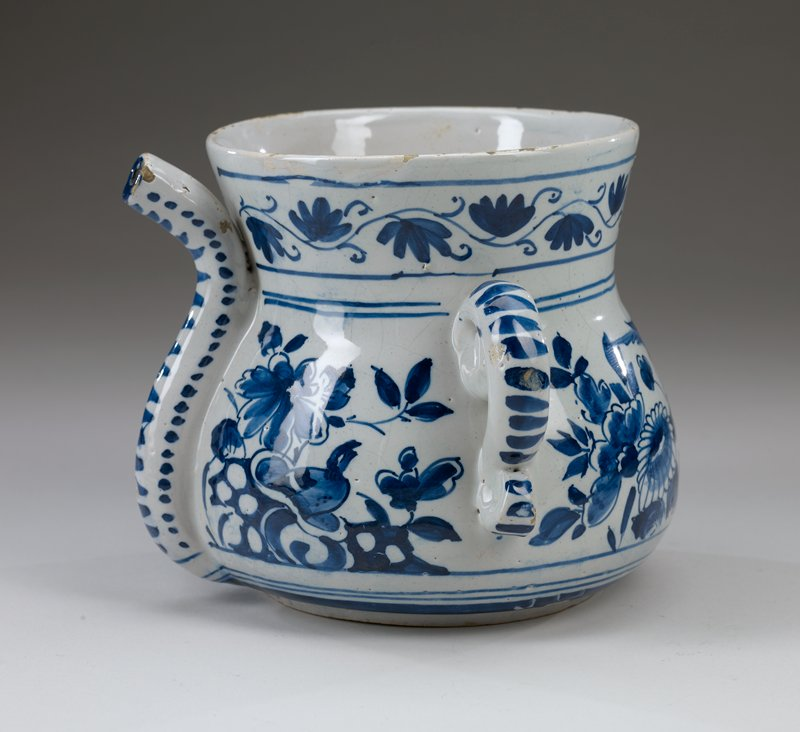 wide-bottomed pot with short ring foot; body tapers inward to short out-ward flaring neck; pair of scrolling handles; long spout attached flush to body; blue and white with bird and flower decorations on body; ring of scrolling flowers around neck