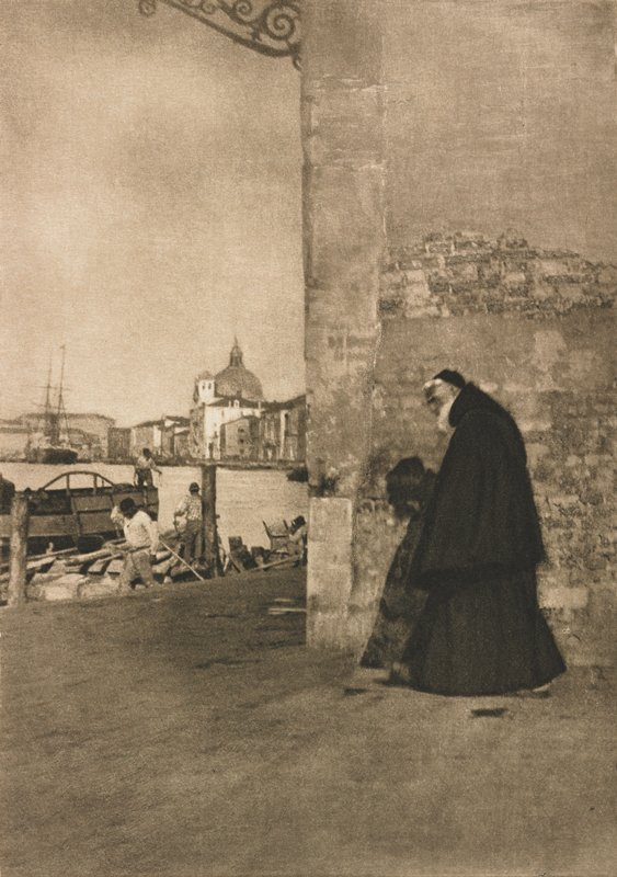 Franciscan monk walks alongside a brick building toward a canal