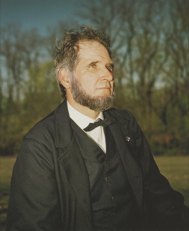 portrait of green-eyed, bearded man dressed as President Lincoln; man looking up; pin with gold cross and American flag on PL lapel; blurry trees with blue sky behind in background; framed behind glass in black wood frame; one of a set of 18 photographs to be displayed together
