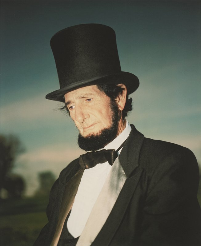 portrait of purple-eyed, bearded man from chest up; man dressed as President Lincoln and facing slightly to PR with head tilted down; blurry trees at LL in distance; blurry clouds and blue sky in background; framed behind glass in black wood frame; one of a set of 18 photographs to be displayed together