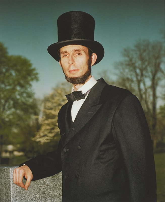waist up portrait of brown-eyed, bearded man dressed as President Lincoln; PR arm rests on gravestone; blurry trees and blue sky in distance; framed behind glass in black wood frame; one of a set of 18 photographs to be displayed together