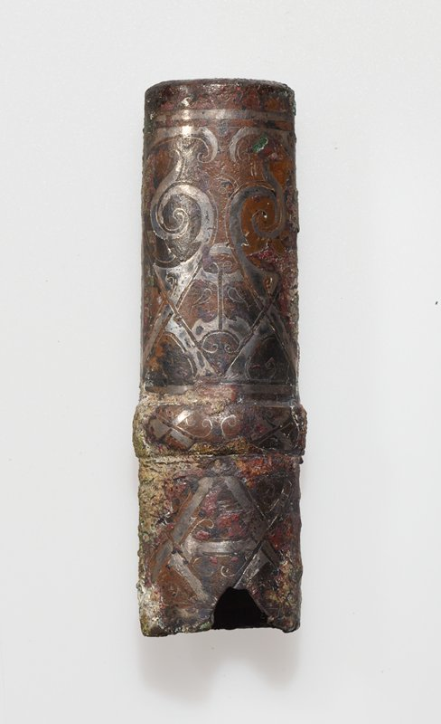 The zoomorphic decor, strongly stylized and inlaid with siver, is divided into three fields by a broad, rounded raised band. Finials of this type, oval in cross-section, were designed for the ends of lance hafts. For an extended discussion of these and similar butt caps, see Karlbeck, Selected Objects from Shou shou, BMFEA, Number 27, Stockholm, 1955. Patina reddish-brown with green patches- one side much corroded.