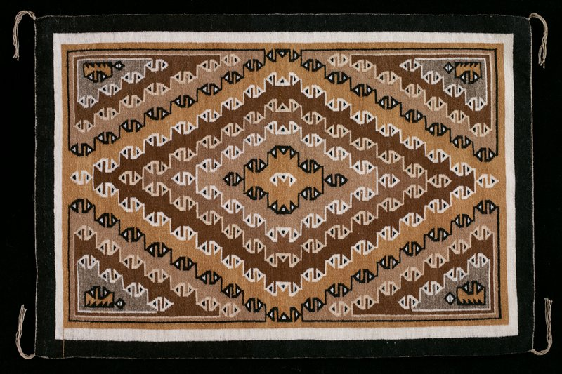 small weaving in black, light tan, medium tan, brown, white and grey, with grey edging and thin grey tassels at corners; geometric design of radiating diamonds with triangle motifs. Former Classification: Textiles - Tapestry