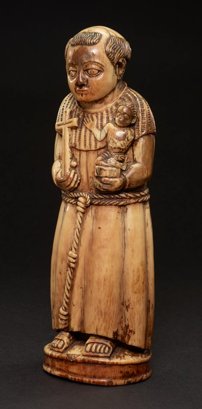 standing figure holding Christ child who sits on a book (?) in saint's PL hand; saint holds cross in PR hand; figure wears a robe with a wide collar, tied with a twisted belt, and sandals