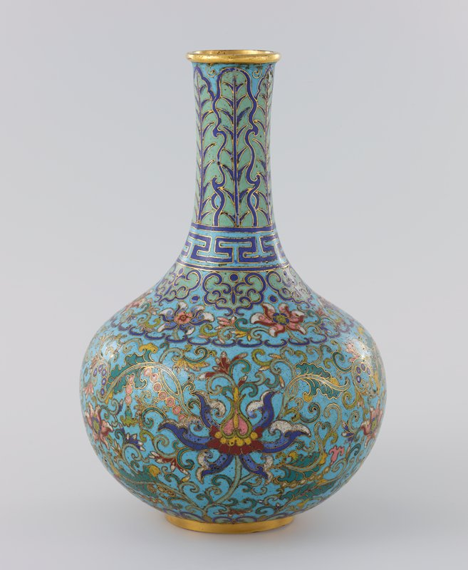 cloisonné bottle; rounded bottom section on gold ring foot; shoulder tapers to long spout which slightly flares outward at top to ring mouth; floral, leaf, and scroll designs, with dark and light blue band with geometric pattern at base of spout