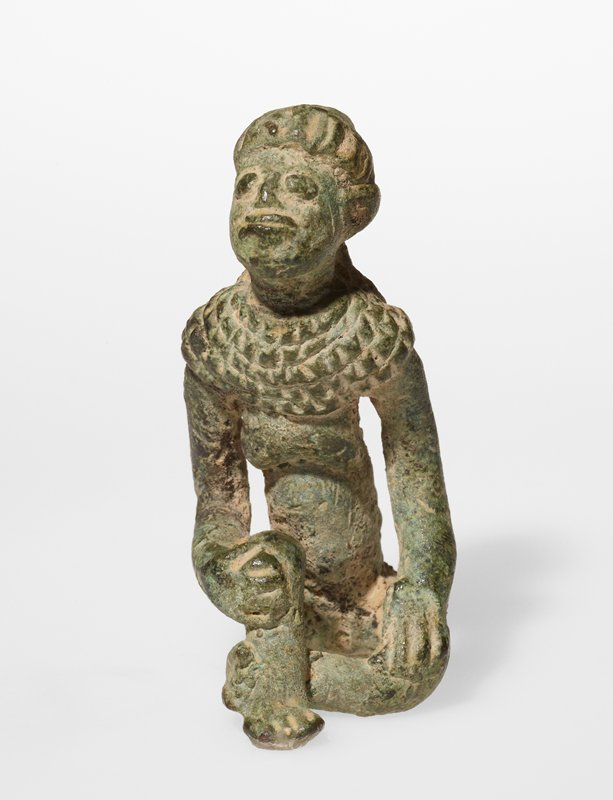 seated woman wearing a thick scarf tied around her head, with the tail trailing down her back; woman also wears a wide collar or necklace; bare breasts; figure has one knee drawn up and the other leg down, with knee bent; one hand on each knee; green and brown patina