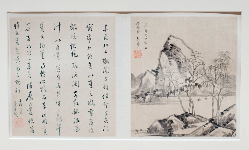two album leaves mounted on boards and matted; left is calligraphic; right is landscape with mountains in background, three trees in center middle ground, two smaller trees to right in foreground with rocks, waterfall, and river from accordion-style album, wood covers; eight images, alternating with text, single page of text at end