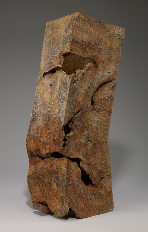 abstract rectangular object with separate wedge; hollow wood burl with crack like openings and holes; wedge positioned under larger piece and protrudes on one side only and is for visual balance not stability