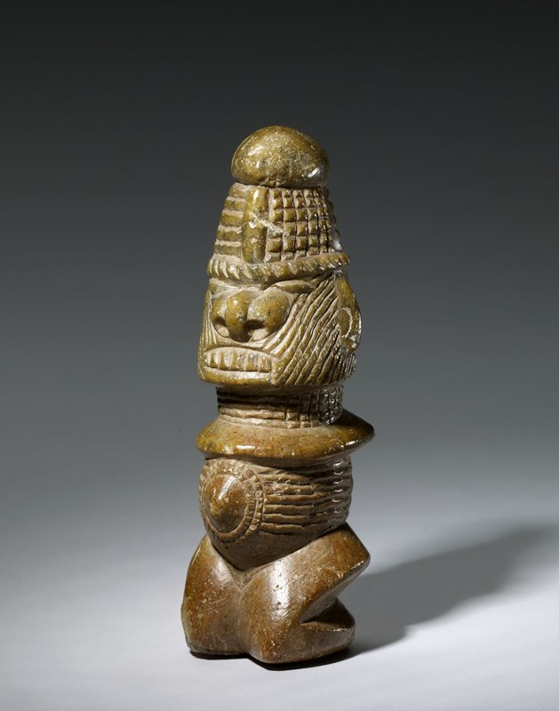 stylized armless figure with large nose with flaring nostrils, closed eyes and gritted bared teeth; wedge-shaped hat; figure kneels with stylized legs; pointed belly button; body, head and hat covered with incised lines, grids, wedge shapes and radiating diamonds; tan-colored stone