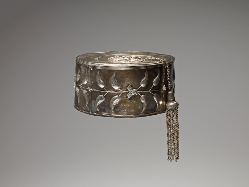 ovoid shaped with flat top; chain extending from top center with tassel made of many hanging chains; central top high relief design of flower surrounded by five-pointed stars; sides decorated with relief designs of regularly-spaced leaves extending off flat horizontal vines