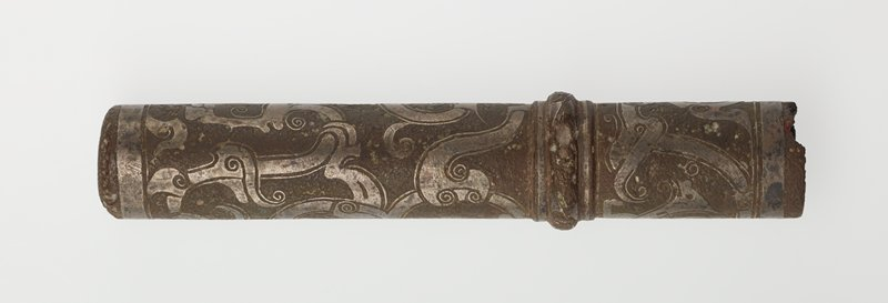 The cylindrical tube with rounded bottom is cirular in cross section. A rounded band near the open end divides it into three areas of decor, the upper and lower filled with stylized birds in broad bands of silver inlay and silver threads. Patina reddish-brown. Bronze with silver inlay.