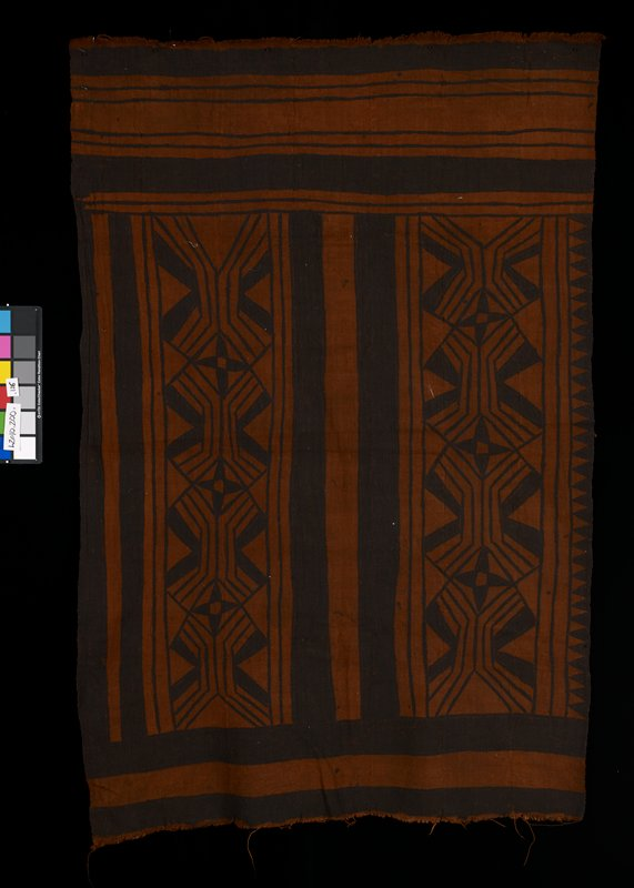 brown and black textile decorated with stripes and geometric designs, including triangles along the edges and stars toward the center; shorter edges have fringe; constructed of seven long strips stitched together