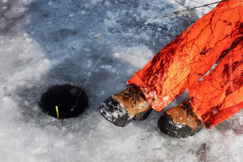LON139184; caption: USA. Minnesota. Minneapolis. Winter Games. Ice Fishing. 2012.; color image of ice fishing hole at L with orange pant bottoms and brown and black boots at R; tip of black fishing rod at top R with line and bobber into ice hole