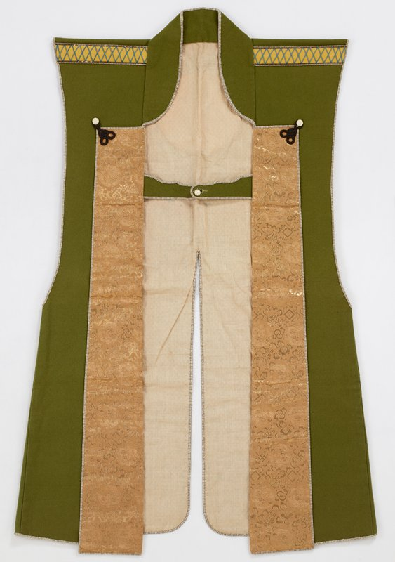 vest-like garment; green wool; horizontal tab with button closure on chest; black frogs with white button holds down vertical front flaps at upper chest; front flaps are metallic gold and tan brocade; yellow wool elements on shoulders embellished with blue crisscross stitching; white wool applique on upper back of three leaves inside a circle; off-white lining fabric woven with white-on-white diamond patterns