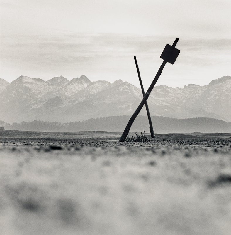 silhouette of crossed posts--one with small square sign; mountains in background