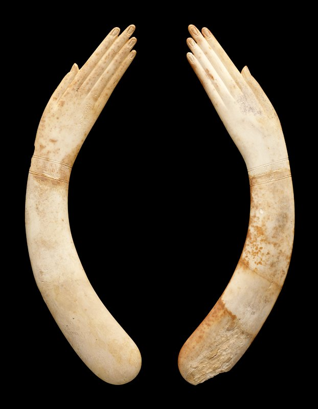 curved; each clapper in the shape of a thin human arm and hand with long, thin fingers; incised bracelets at each wrist with linear patterns; ivory colored with some tan spotting