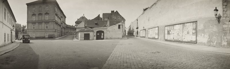 deserted city street with parked truck at left; cobblestones at right; wall with four billboards plastered with handbills at right; a few people at right in distance in front of arched doorway
