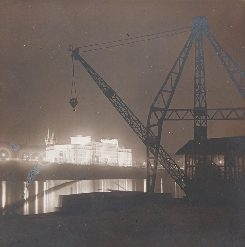 silhouette of crane on scaffolding at right and center, foreground; glowing building at center left beyond water