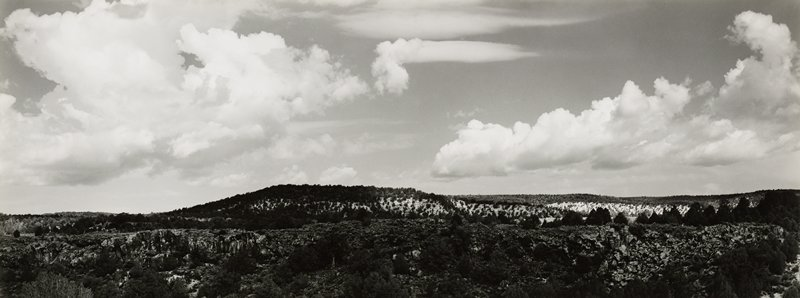 low hill with trees; rocky land in foreground with trees; low horizon line; clouds