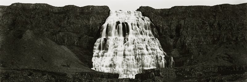 waterfall cascading down multiple levels of rock; dark rocks at left and right