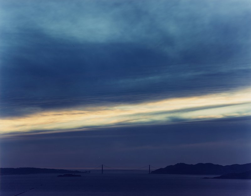 view of suspension bridge (Golden Gate?) across water; island at left; low horizon line; dusk, with line of glowing yellow clouds