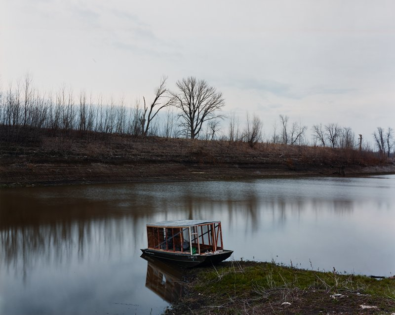 "small boat with homemade ""topper"" roof on the grassy bank of a lake; line of bare trees in middle ground"