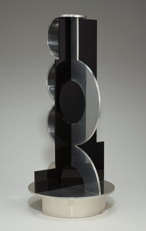 upright sculpture with flat, black, central Plexiglas core with irregularly stepped edges; on one side are three stacked, wide half-circles in polished aluminum; other has one large, flat, polished aluminum arc with another half-arch below touching base; attached to a round polished aluminum base with a foot ring on half of base and a vertical support from center to outer edge under other half of base; shiny black and silver