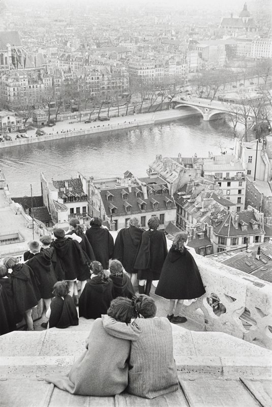 people at a lookout point at corner of Notre-Dame cathedral; seated couple in foreground, seen from back--man has his PL arm around woman's neck; group of children wearing dark hooded capes looking over Paris and Seine from railing; three little girls seated