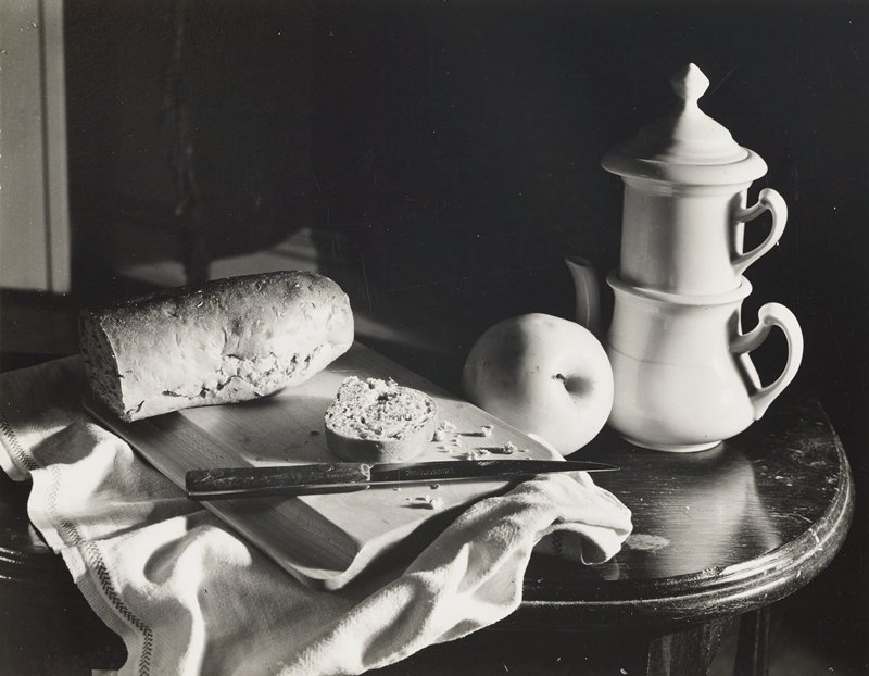 still life with loaf of bread and knife on cutting board, apple and teapot with a covered teacup on top
